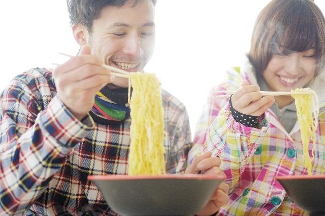 麺を一緒にご飯友達と食べる男女